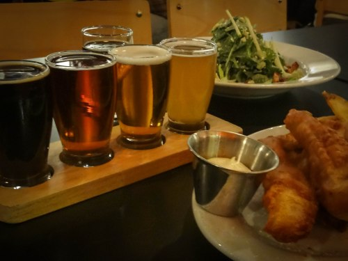 a flight of beers, arugula salad, and impeccable fish and chips with aioli