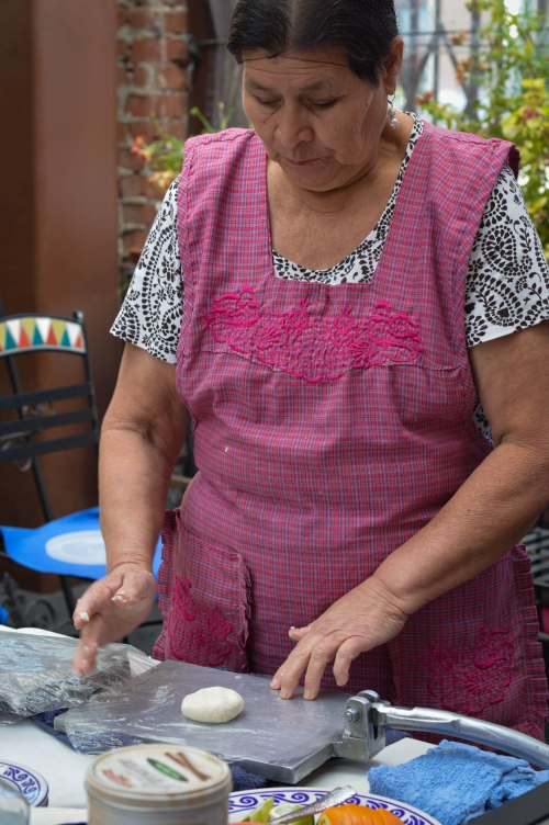 Doña Libo Gomez creates all of the recipes. Here, she demonstrates making tortillas by hand.